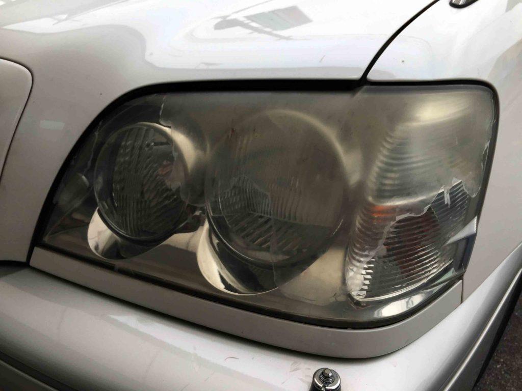 トヨタクラウンのヘッドライトレンズが劣化しコーティング層が剥がれています