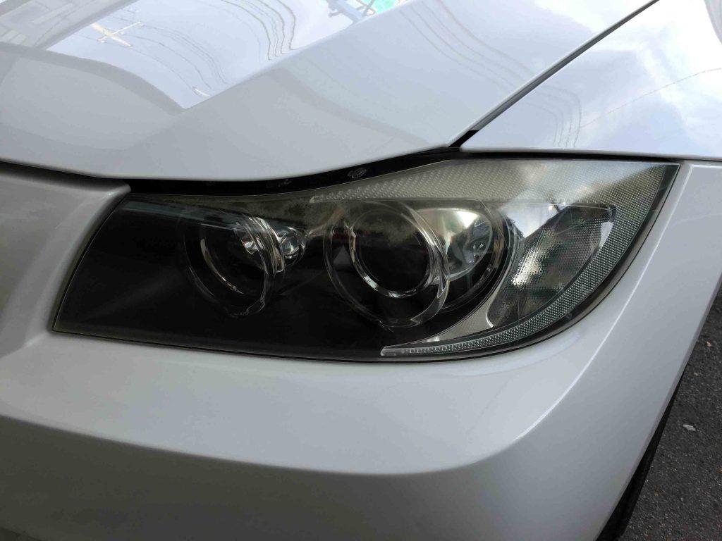 BMW E90 3シリーズの劣化し黄ばんだヘッドライト。上部が特に劣化が進行しています。