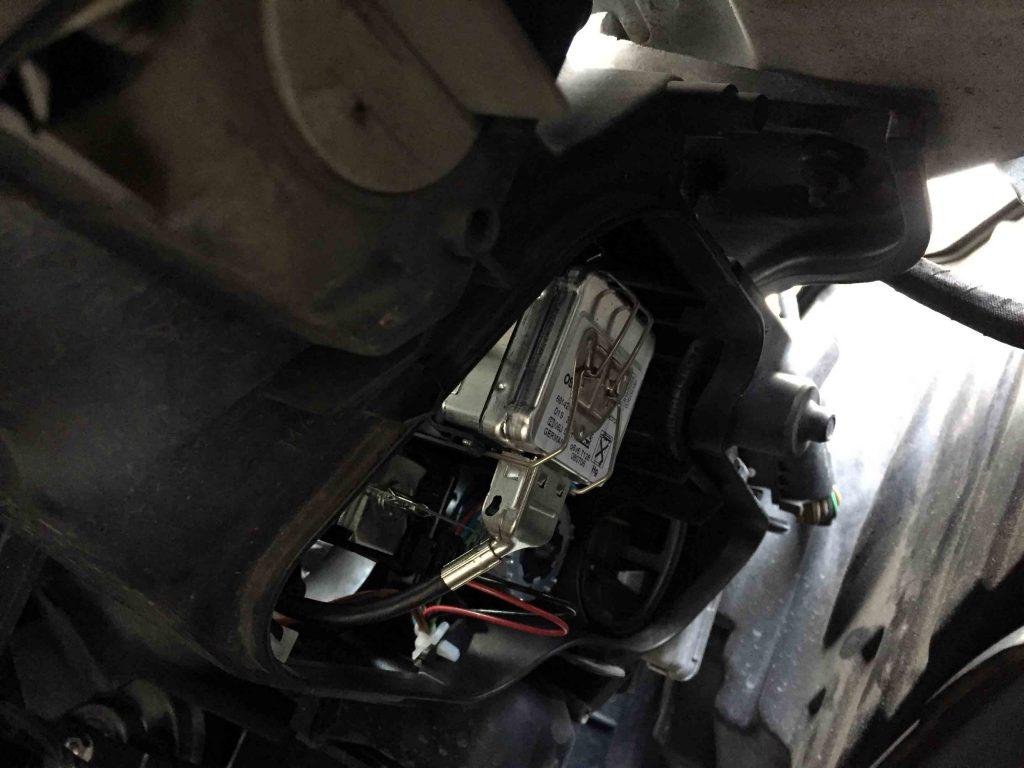 BMW E91 3シリーズのヘッドライト裏蓋を外します。