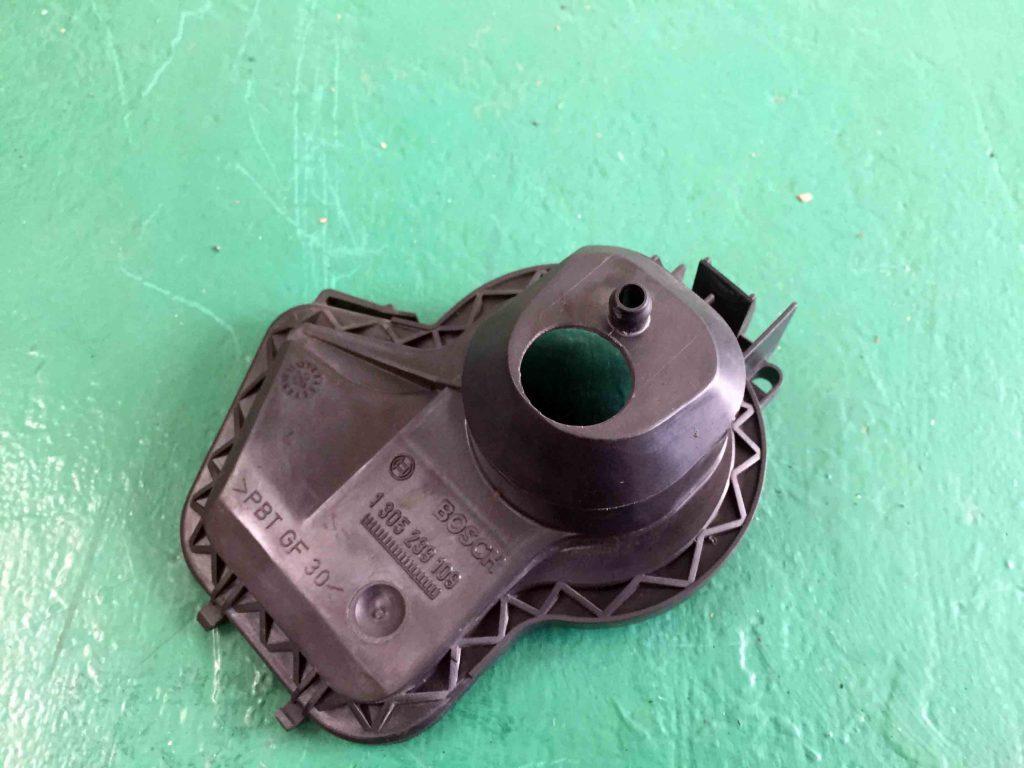 フォルクスワーゲン前期型ニュービートルのヘッドライト裏蓋に配線を通す穴を開けます。