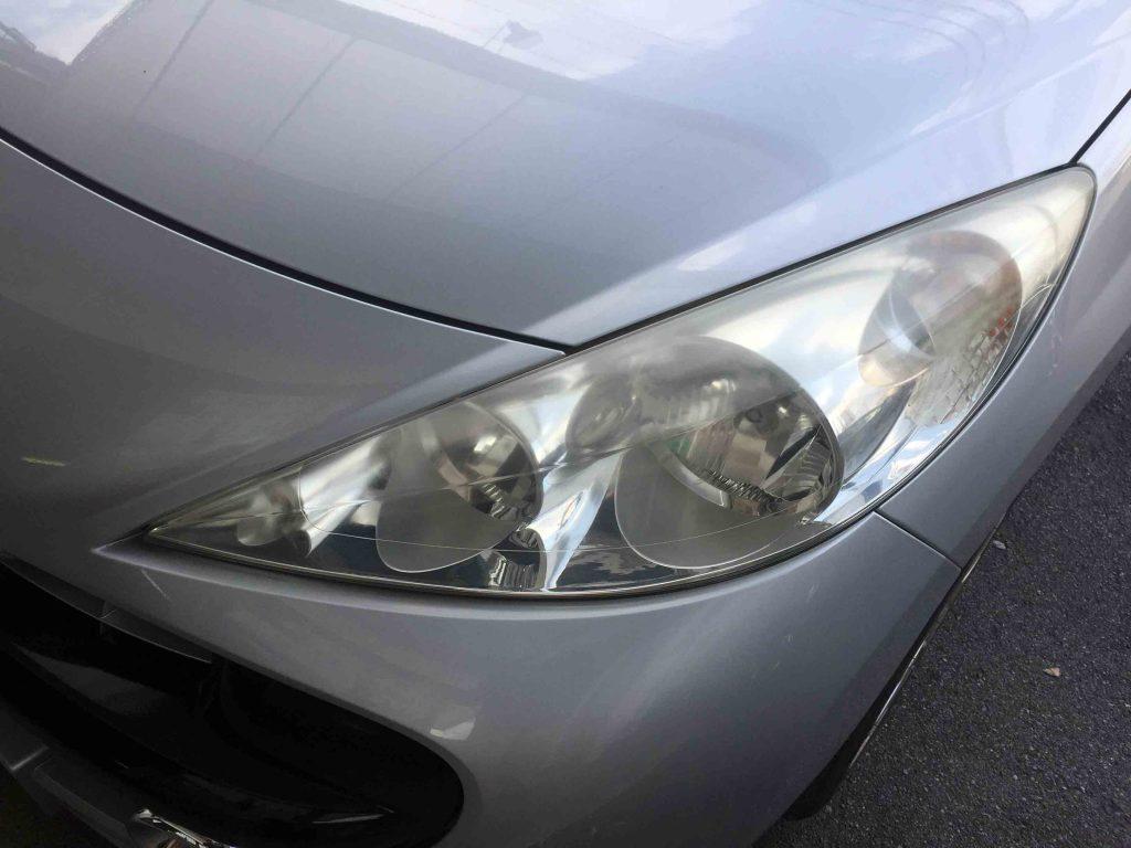 プジョー207の劣化し黄ばみが発生したヘッドライト上部は特に劣化が進行しています。
